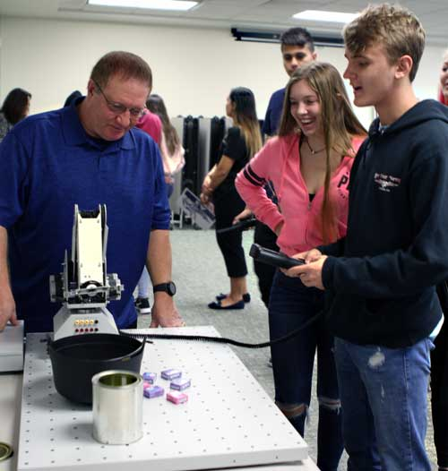 SJR State instructor Robert Frank explains to Clay County school students how to operate robotic equipment at the Engineering Technology tour stop during