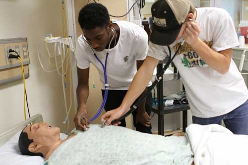 Clay County high school students listen to the heartbeat of a mannequin patient in the nursing lab at St. Johns River State College.