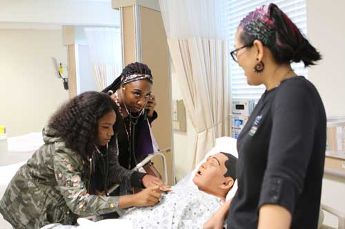 St. Johns River State College nursing professor Charlene Velasco observes as Clay County high school students listen to the heartbeat of a mannequin patient in the College's nursing lab on Career Day.