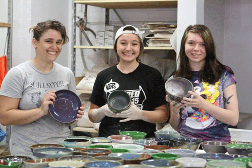 Florida School of the Arts students Lydia Borko, Ana Edwards and Sabryna Hesse show a few of the bowls created by students for the Empty Bowls Project""