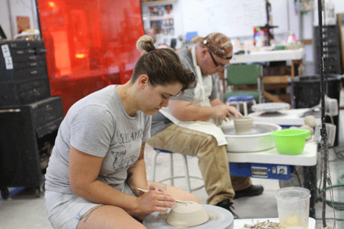 Florida School of the Arts student Lydia Borko and alumnus Cody Burke diligently create bowls for the Empty Bowls Project""