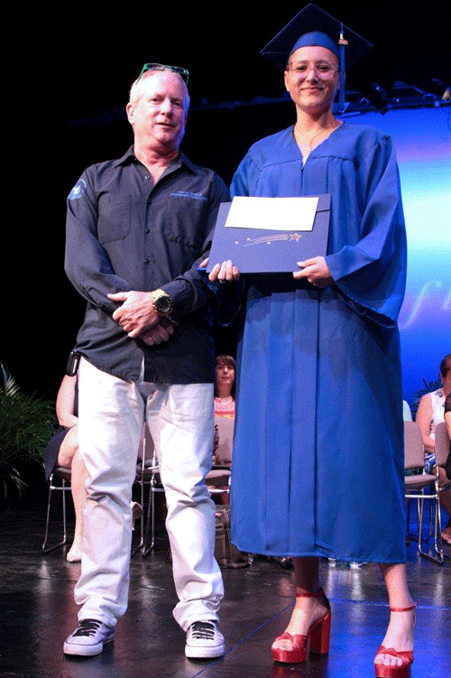 instructor Dan Askew presents Caitlin Pecknold wit the Outstanding Graduate in the Visual Arts award