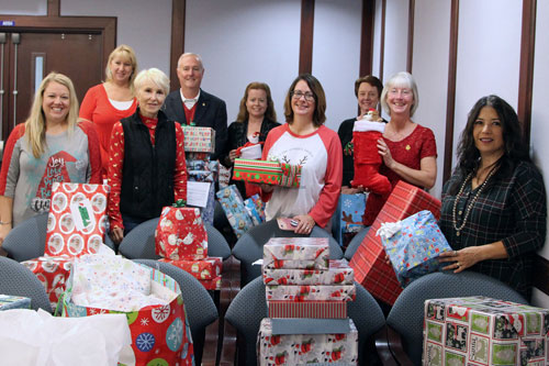 SJR State employees and members of the Putnam County School District stand among gifts to be delivered to needy children this Christmas as part of an annual charity program of Project PRAISE