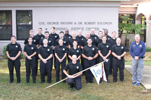 law enforcement cadets Kneeling with Flag: A. Houser; First Row, L - R: D. Jarousse (Class Leader), S. Fultz (Squad Leader), C. Cruzpeña, K. Gordon (Scribe), A. Narsico, R. Cassidy, J. Hinton, A. Cuthbert (Guidon), John Donlon (Instructor/Coordinator); 2nd Row, L - R: J. Crawford (Squad Leader), M. Ofsanik, C. Prescott, L. Stack, L. Burke, R. Forrest, K. Rubright; Back Row, L - R: J. Gregos (Squad Leader), M. Reddington, N. Burchell, P. Davis, A. Canaan, M. James