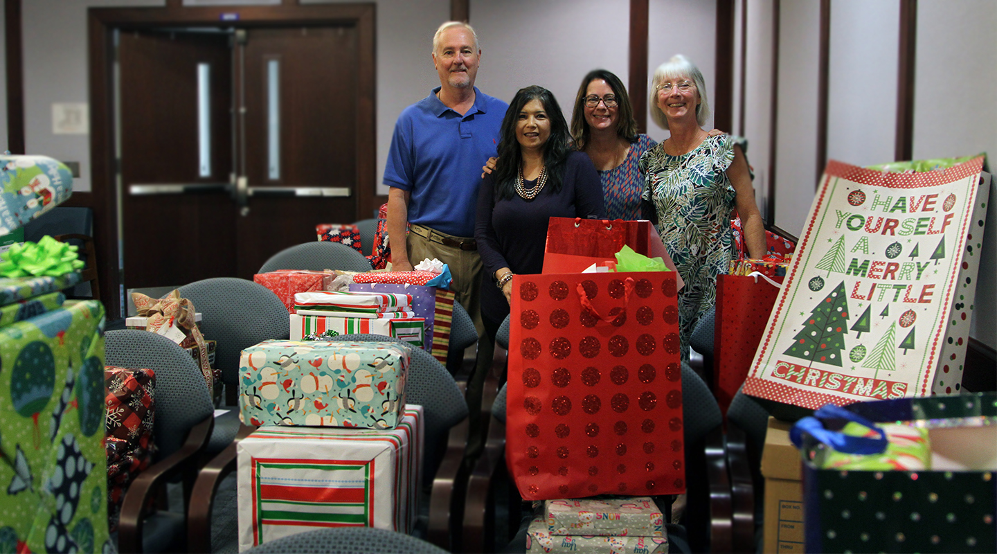 SJR State employees stand among gifts to be delivered to needy children this Christmas as part of an annual charity program of Project PRAISE