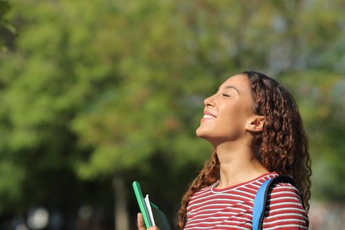 girl looking up with sun on her face